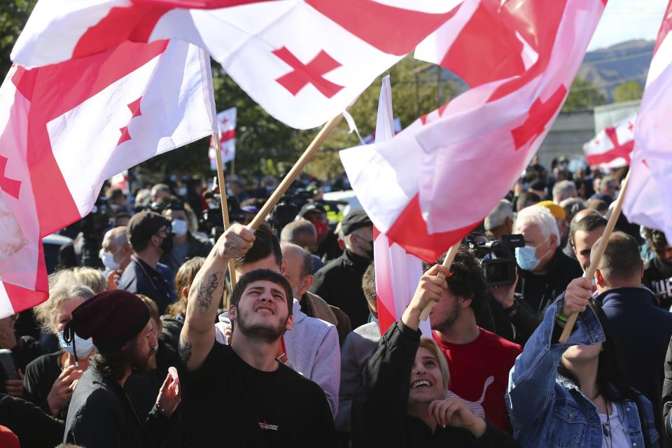 Georgian opposition supporters of former president Mikheil Saakashvili wave Georgian national flags during a rally in his support in front of the prison where former president is being held, in Rustavi, about 20 km from the capital Tbilisi, Georgia, Monday, Oct. 4, 2021. Saakashvili was detained in Tbilisi on Saturday, Oct. 1, 2021. Georgia earlier declared Saakashvili wanted as a person convicted in absentia in several criminal cases and treated as a suspect in some others. Georgian authorities have warned repeatedly that he would be detained immediately once over the border. (AP Photo/Zurab Tsertsvadze)