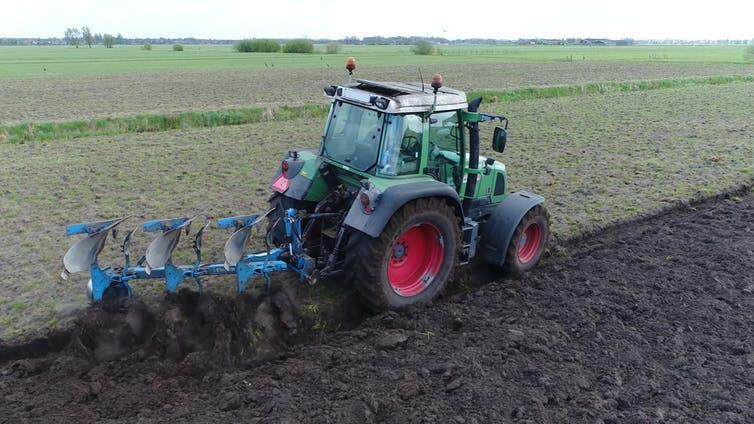 A green tractor uses a trailer to till the soil behind it.