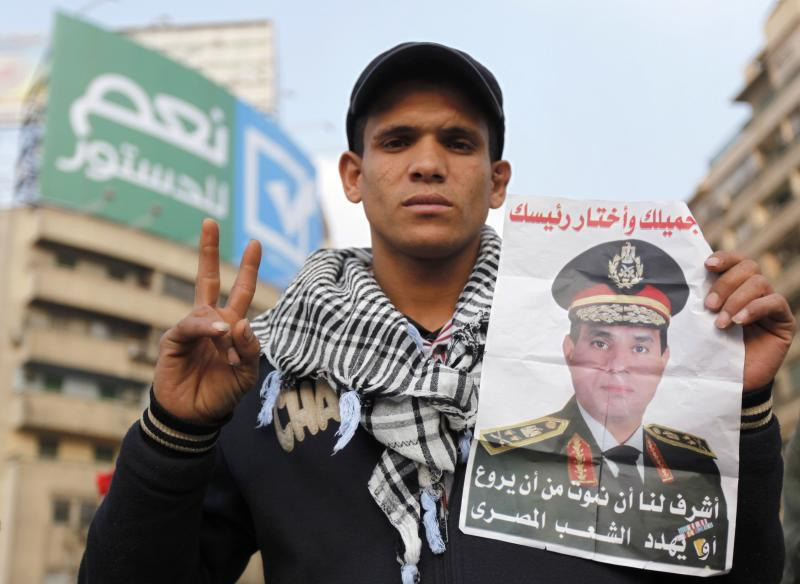 A supporter of Egypt's army chief and defense minister General Abdel Fattah al-Sisi holds a poster with Sisi's image during a protest in support of the new constitution at Tahrir Square in Cairo December 20, 2013. Egyptians will vote on a new constitution on Jan. 14 and 15, pushing on with the army-backed government's plan for transition back to democracy after its overthrow of elected Islamist President Mohamed Mursi. REUTERS/Mohamed Abd El Ghany (EGYPT - Tags: CIVIL UNREST MILITARY POLITICS)