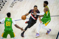 Portland Trail Blazers forward Norman Powell (24) drives the ball on Utah Jazz guard Donovan Mitchell, right, during the first half of an NBA basketball game Thursday, April 8, 2021, in Salt Lake City. (AP Photo/Isaac Hale)