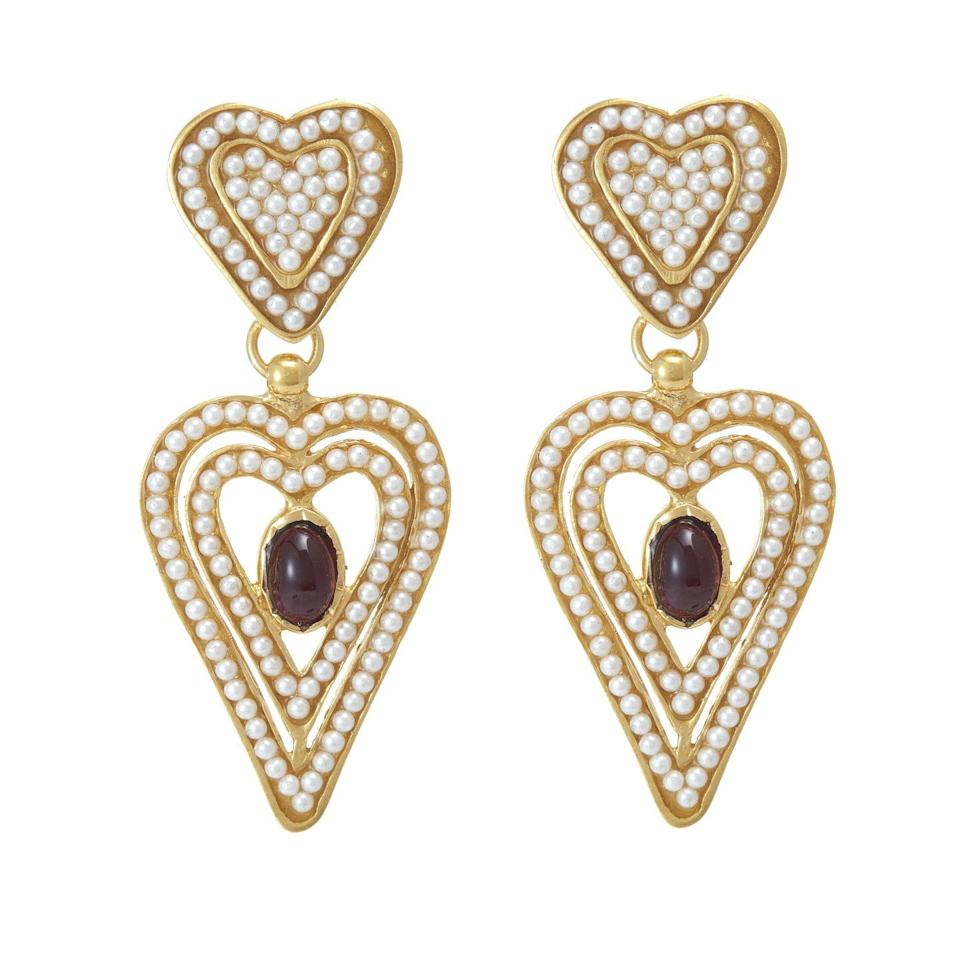 "<p>Soru Jewellery's golden Amore earrings are hand-set in Italy with miniature pearls and red garnet stones – a gem used since the Bronze Age said to inspire self-confidence.</p><p>£155, Soru Jewellery</p><p><a class=""link rapid-noclick-resp"" href=""https://www.sorujewellery.com/collections/gifts-with-meaning/products/nc-pearl-heart-earrings"" rel=""nofollow noopener"" target=""_blank"" data-ylk=""slk:SHOP NOW"">SHOP NOW</a></p>"