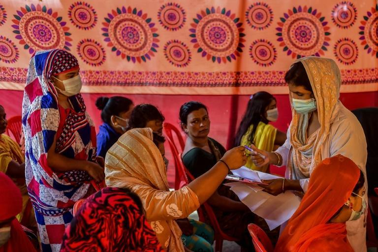 A health official registers the details of sex workers who gathered to get themselves inoculated in Daulatdia