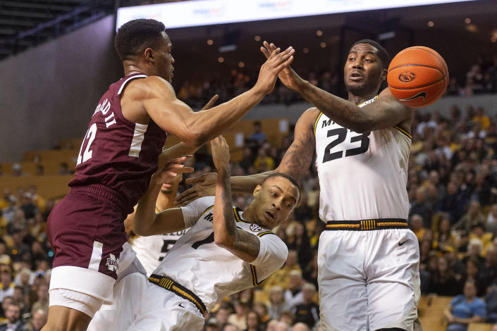 Mississippi State's Robert Woodard II, left, fouls Missouri's Xavier Pinson, center, as he shoots over Missouri's Jeremiah Tilmon, right, during the first half of an NCAA college basketball game Saturday, Feb. 29, 2020, in Columbia, Mo. (AP Photo/L.G. Patterson)