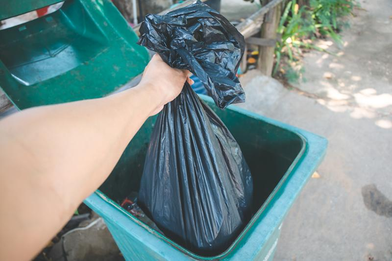 A person places a black garbage bag in a bin. A woman in England was arrested for using the wrong bin bags. She used black ones instead of clear and orange ones to separate her waste.