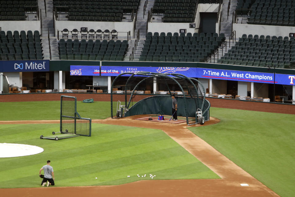 Unidentified players workout at Globe Life Field, home of the Texas Rangers baseball team, in Arlington, Texas, Monday, June 1, 2020. The coronavirus pandemic has forced universities, leagues and franchises to evaluate how they might someday welcome back fans. At baseball games in Taiwan, up to 1,000 spectators have been allowed into the ballpark, but they are barred from bringing in food, concession stands are closed and they are told to sit three seats apart. (AP Photo/LM Otero)