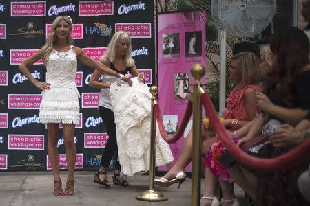 Designer and model Susan Brennan of Orchard Lake, Michigan is helped by an assistant while modeling during the 10th annual toilet paper wedding dress contest in Midtown, New York June 12, 2014. REUTERS/Adrees Latif