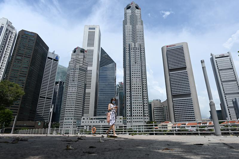 A woman walks past commercial buildings in the financial business district in Singapore on June 11, 2020, as the city state eased its partial lockdown restrictions aimed at curbing the spread of the COVID-19 coronavirus. (Photo by ROSLAN RAHMAN / AFP) (Photo by ROSLAN RAHMAN/AFP via Getty Images)