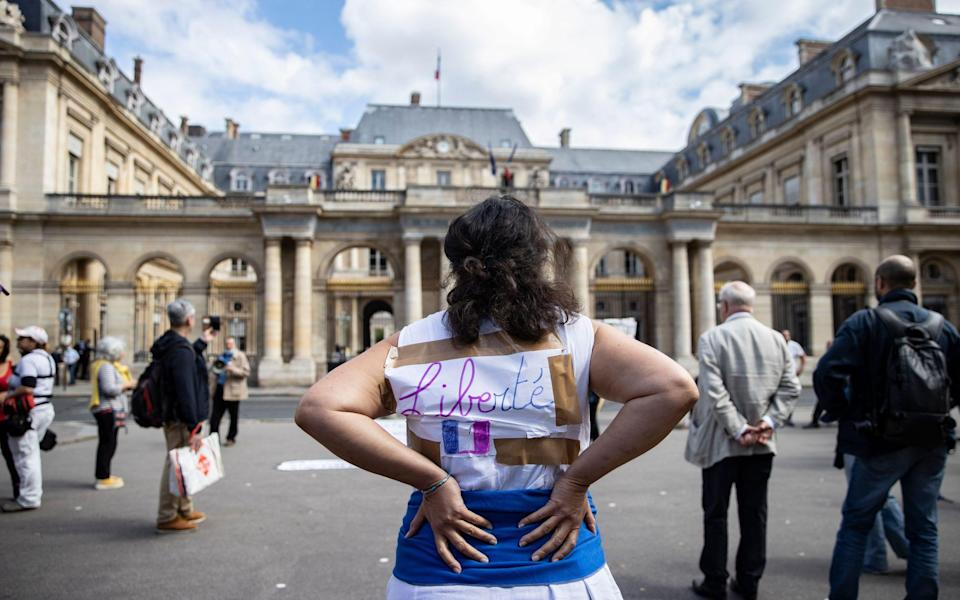 Protesters railing against Covid passports gathered outside the French Constitutional Council earlier, such as this one displaying 'liberty' on her jacket - IAN LANGSDON/EPA-EFE/Shutterstock