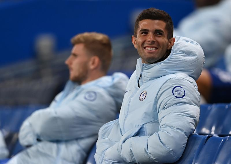 Christian Pulisic looks on and smiles from the stands during the Carabao Cup.
