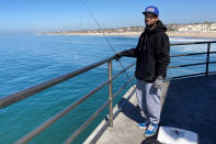 Michael Archouletta, 29, said he came down to Huntington Beach from East Los Angeles early to fish and didn't see any signs barring him from fishing on the pier in Huntington Beach, Calif., Sunday, Oct. 10, 2021. Fishing has been closed along the shore since an offshore pipeline was found leaking oil into the Pacific Ocean waters off the coast of Orange County. (AP Photo/Amy Taxin)