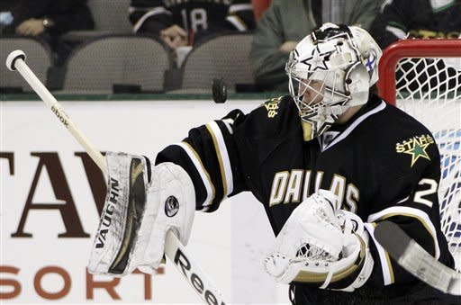 Dallas Stars' Kari Lehtonen (32), of Finland, keeps his eyes on an airborne puck in the second period of an NHL hockey game against the Vancouver Canucks, Sunday, Feb. 26, 2012, in Dallas. (AP Photo/Tony Gutierrez)