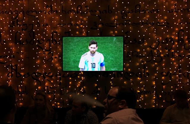 Soccer Football - World Cup - Group D - Argentina vs Croatia - Saint Petersburg, Russia - June 21, 2018. People sit in a restaurant as Argentina's Messi is seen on a tv screen at the end of their match against Croatia. REUTERS/Marcos Brindicci