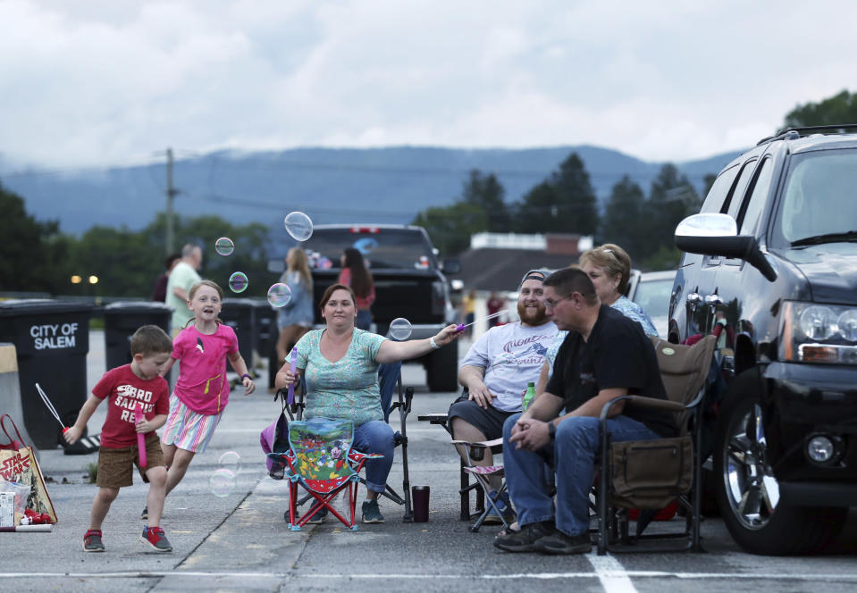 Alice Carr, 7, and her bother Bruce Carr, 3, chase bubbles being made by their mom, Olivia Carr, with their dad, Brandon Carr, and grandparents Rhonda and Eric Carr during a drive-in concert with Crawford & Power in the Salem Civic Center parking lot Thursday, June 18, 2020, in Salem, Va., amid the coronavirus pandemic. (Heather Rousseau/The Roanoke Times via AP)