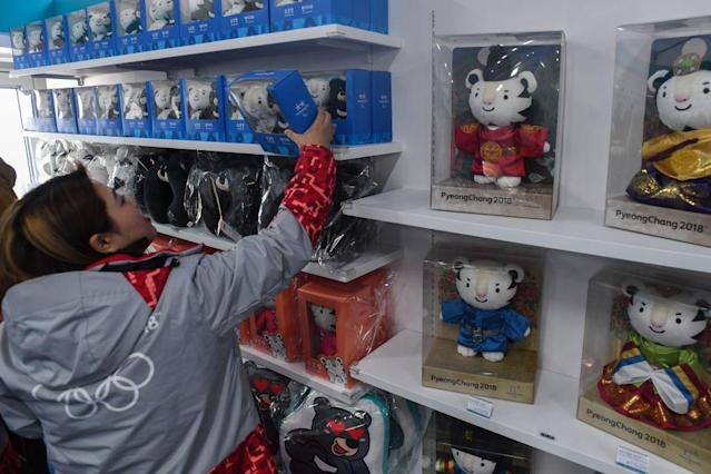 A worker is stocking the shelves with souvenirs for the 2018 Winter Olympic Games in PyeongChang, South Korea. (Getty)