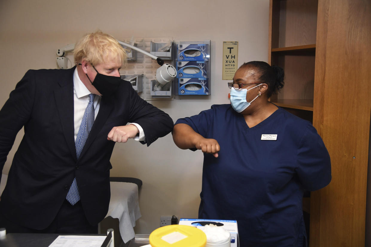 Britain's Prime Minister Boris Johnson, left, elbow bumps Lead Nurse Marina Marquis, during a visit to Tollgate Medical Centre in Beckton, East London, Friday July 24, 2020. (Jeremy Selwyn/Pool Photo via AP)