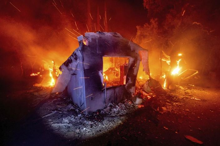 """Flames from the LNU Lightning Complex fire consume a home in Napa County on Aug. 19. <span class=""""copyright"""">(Noah Berger / Associated Press)</span>"""