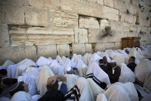 Jewish men pray at the Western Wall in the Old City of Jerusalem on March 28, 2013