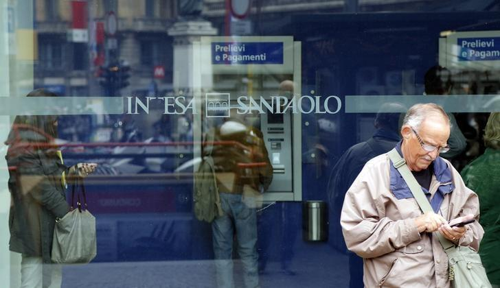 A man stands outside a building as people use Intesa Sanpaolo automated teller machines (ATMs) in Milan