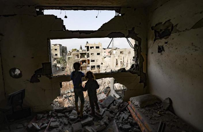 Children standing on rubble in a bedroom look through a shattered wall at ruined buildings.