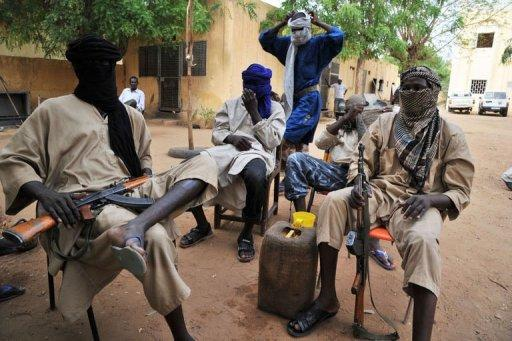MUJAO Islamist fighters sit in the courtyard of the Islamist police station in Gao in July 2012