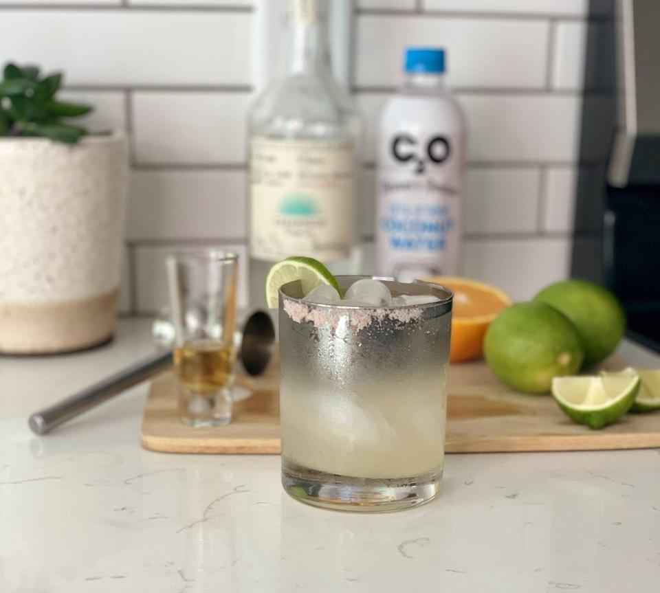 """<p>If you're looking for something hydrating and light that will give you a buzz, we recommend this <a href=""""https://www.popsugar.com/food/Best-Margarita-Recipe-46273376"""" class=""""link rapid-noclick-resp"""" rel=""""nofollow noopener"""" target=""""_blank"""" data-ylk=""""slk:coconut water margarita"""">coconut water margarita</a>. The key is to naturally sweeten it with a fresh squeeze of orange juice!</p> <p><strong>Ingredients: </strong></p> <ul> <li>1.5 oz of premium blanco tequila (Casamigos used here)</li> <li>0.5 oz of Grand Marnier</li> <li>1 lime, juiced</li> <li>1 orange wedge</li> <li>1 splash of fresh coconut water</li> </ul> <p><strong>Directions</strong>: Take a lime wedge and use it rub the rim on the edge of a rocks-glass. Then, dip it into some freshly ground pink Himalayan salt. You won't need too much because the saltiness is a very strong flavor. Next, combine all remaining ingredients into a cocktail shaker with ice. Once mixed, pour over fresh ice in your salted rocks-glass. Garnish with a lime wedge and enjoy!</p>"""