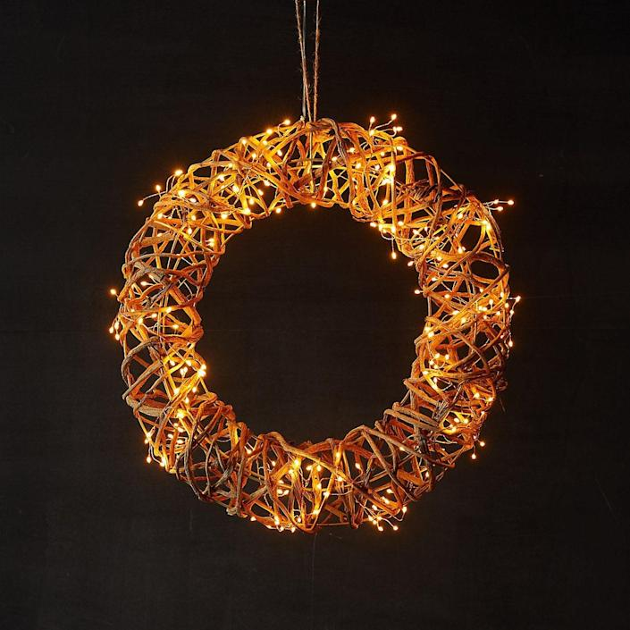 """This rattan- and LED light–covered wreath adds a warm and fiery glow. $69, Terrain. <a href=""""https://www.shopterrain.com/products/pre-lit-led-rattan-vine-wreath"""" rel=""""nofollow noopener"""" target=""""_blank"""" data-ylk=""""slk:Get it now!"""" class=""""link rapid-noclick-resp"""">Get it now!</a>"""
