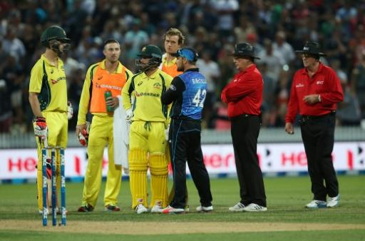 Australia's Mitchell Marsh (L) and Matthew Wade (3rd L) with Brendon McCullum of New Zealand (3rd R) await the umpires decision during the third one-day international cricket match on February 8, 2016