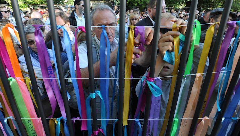 People attach ribbons with Jewish names onto the fence of a former Jewish orphanage,  in Warsaw, Poland, Sunday, July 22, 2012, during commemorations marking the 70th anniversary of first transport of Jews from the Warsaw Ghetto to the Treblinka death camp during World War II. ( AP Photo/Alik Keplicz)
