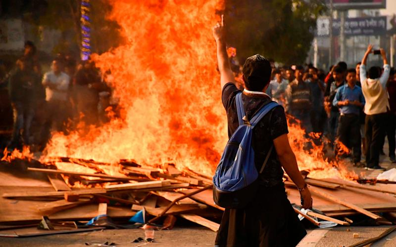 Demonstrators setup a bonfire on a street as they protest against the governments Citizenship Amendment Bill - AFP