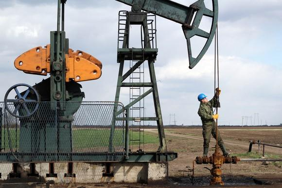 A roughneck working on a pumpjack.