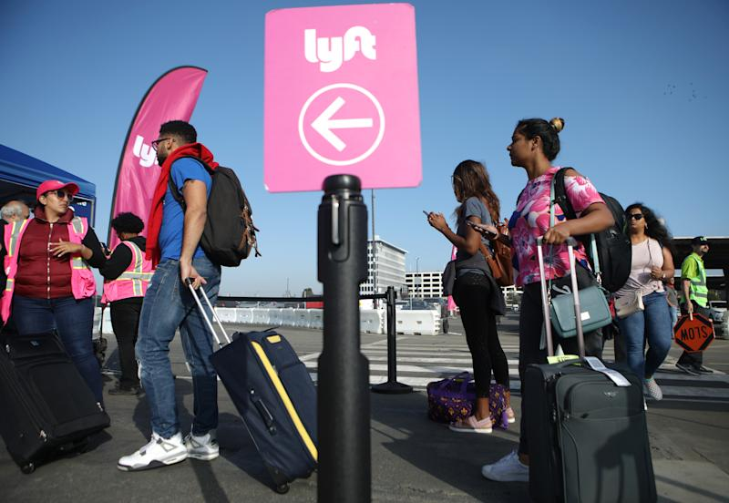 LOS ANGELES, CALIFORNIA - NOVEMBER 06: Arriving passengers wait to board Lyft vehicles at the new 'LAX-it' ride-hail passenger pickup lot at Los Angeles International Airport (LAX) on November 6, 2019 in Los Angeles, California. The airport has instituted a ban on Lyft, Uber and taxi curbside pickups as airport construction increases during a modernization program. Passengers have complained of long wait times and confusion at the pickup area, especially during peak hours. Passengers must depart their terminal and then ride a shuttle bus or walk to the separate pickup lot. (Photo by Mario Tama/Getty Images)