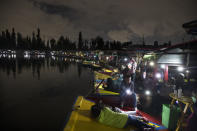 People cast the light of their cellphones from their trajinera boats as they watch the play La Llorona performed on top of a chinampa, a small artificial island at Cuemanco pier in Xochimilco, Mexico City, late Friday, Oct. 9, 2020, as the city promotes the upcoming Day of the Dead holiday at the end of the month, amid the COVID-19 pandemic. Legend has it that La Llorona drowned her children and then regretfully looks for them in rivers and towns, scaring locals who can hear her at night. (AP Photo/Marco Ugarte)