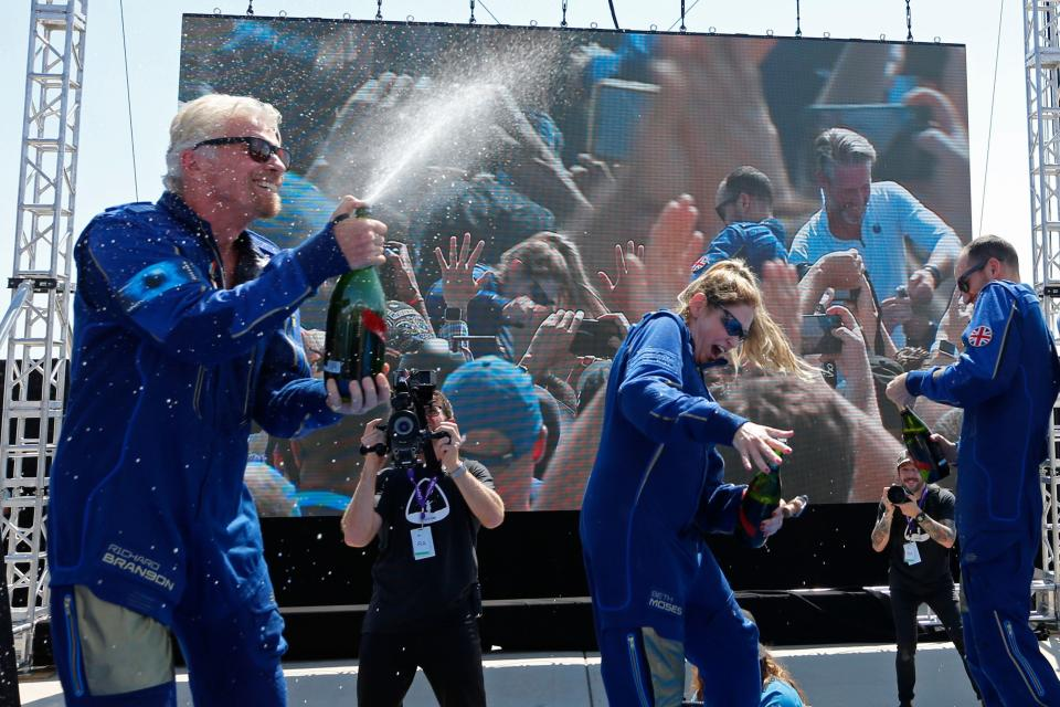Billionaire entrepreneur Richard Branson sprays the crew with champagne after they were announced as astronauts for flying Virgin Galactic's passenger rocket plane VSS Unity to the edge of space at Spaceport America near Truth or Consequences, New Mexico, U.S., July 11, 2021. REUTERS/Joe Skipper
