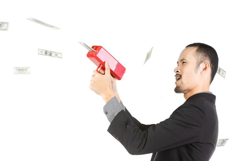 Side View Of Businessman Removing Paper Currency From Machinery Against White Background