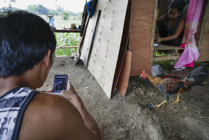 Ronnel Manjares, left, looks at a picture of his son Kobe saved in his smartphone outside their house of their relative in Tanauan, Batangas province, Philippines, Wednesday, July 15, 2020. His 16-day-old son Kobe was heralded as the country's youngest COVID-19 survivor. But the relief and joy proved didn't last. Three days later, Kobe died on June 4 from complications of Hirschsprung disease, a rare birth defect. (AP Photo/Aaron Favila)