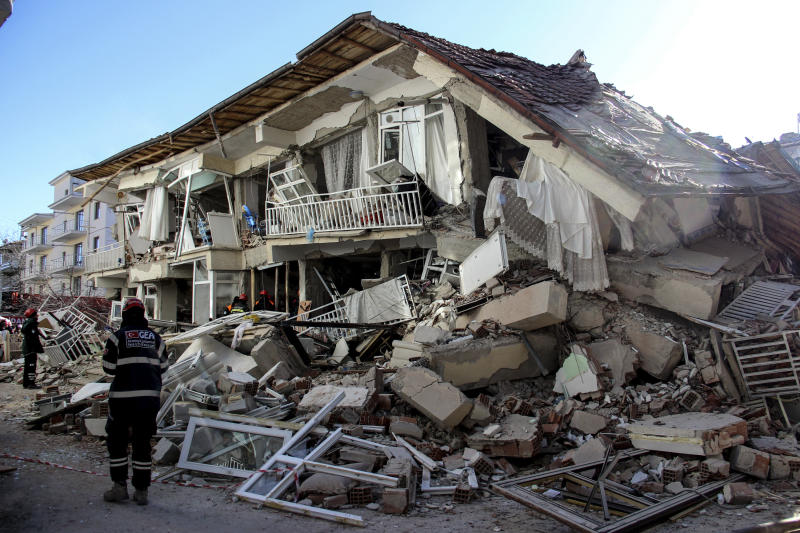 Rescue workers try to reach people under a collapsed building following a strong earthquake in Elazig in the eastern Turkey, Saturday, Jan. 25, 2020. The earthquake rocked eastern Turkey on Friday, causing some buildings to collapse and killing scores of people, Turkish officials said. (IHA via AP)