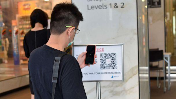 PHOTO: A man scans a QR code before entering a building in Singapore Tuesday, June 2, 2020. Singapore reopened 75% of its economy Tuesday, as part of a three-phase controlled approach to end a virus lockdown since early April. (YK Chan/AP)