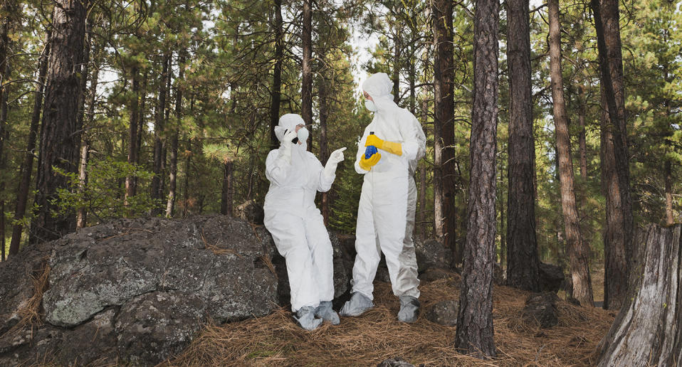 Scientists meeting about secret discoveries/projects in Woods in radiation suits with beaker and cell phone. Source: Getty Stock