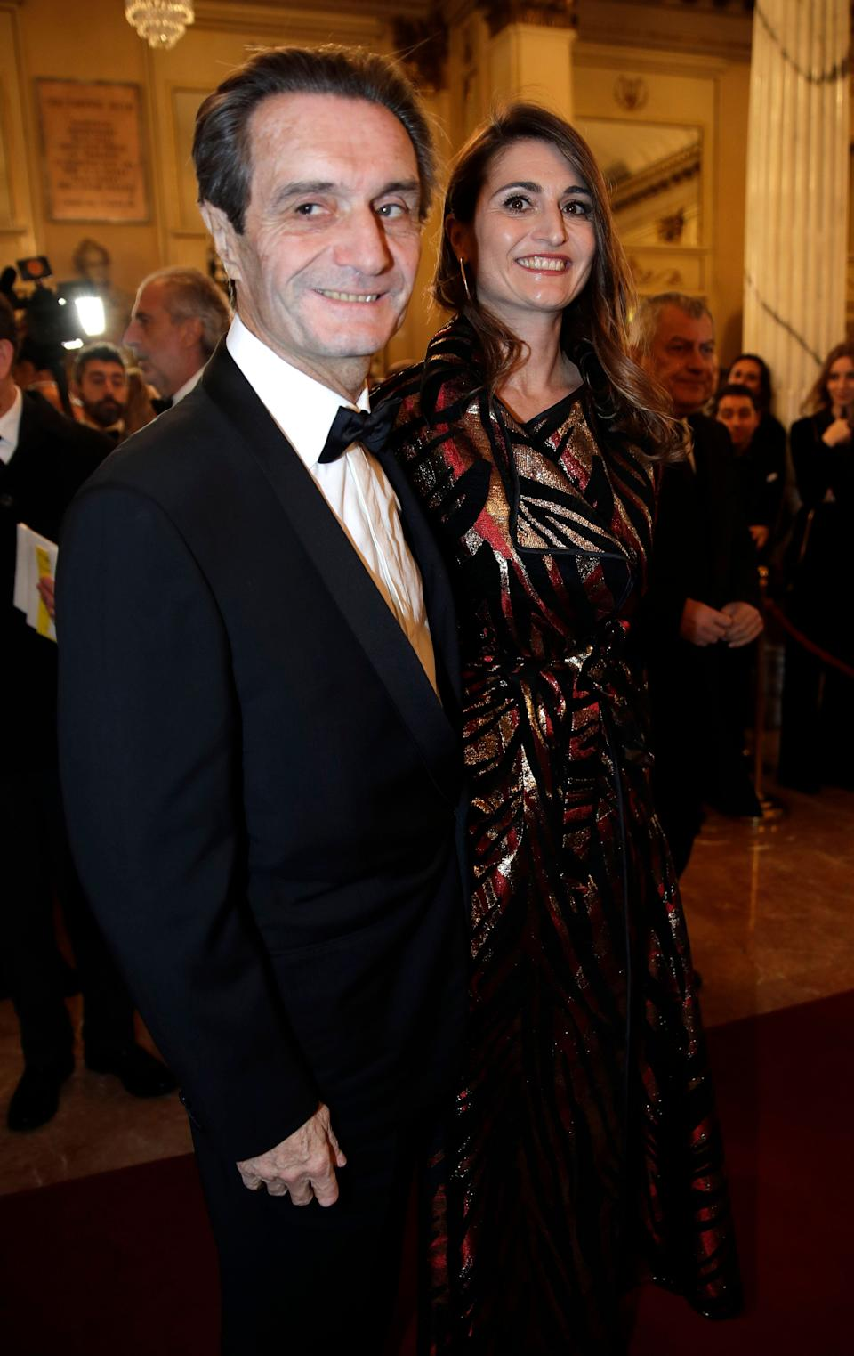 """Lombardy region president Attilio Fontana arrives daughter Maria Cristina flanked by his for the gala premiere of La Scala opera house, in Milan, Italy, Saturday, Dec. 7, 2019. Milan's storied La Scala opens its 2019-2020 season on Saturday with Puccini's """"Tosca,"""" which stars Russian soprano Anna Netrebko as the object of unwanted sexual attention from a powerful authority figure. (AP Photo/Luca Bruno) (Photo: ASSOCIATED PRESS)"""
