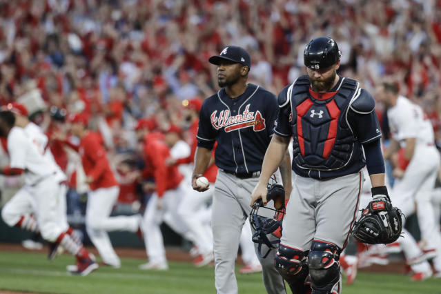 Atlanta Braves' Julio Teheran and catcher Brian McCann walk to the dugout after St. Louis Cardinals' Yadier Molina hit a sacrifice fly to score Kolten Wong for the winning run during the 10th inning in Game 4 of a baseball National League Division Series, Monday, Oct. 7, 2019, in St. Louis. (AP Photo, Charlie Riedel)