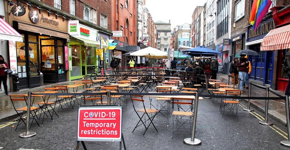LONDON, UNITED KINGDOM - 2020/10/24: Temporary Pedestrian zone sign at the entrance to a cordoned off street in Soho with empty tables and chairs outside a restaurant. Struggling bars and restaurants in London will be at crossroads at the end of this week. It's a few days before the end of the programme of road closures in Soho and Covent Garden that has permitted restaurants and bars to put tables in the streets for the first time. Soho was transformed into an alfresco dining district, but as winter approaches, streets in the cold and rain are virtually empty and with the prospect of a further lockdown many businesses who have tried so hard to make it, look like they are being forced to close up - this time for good. (Photo by Keith Mayhew/SOPA Images/LightRocket via Getty Images)