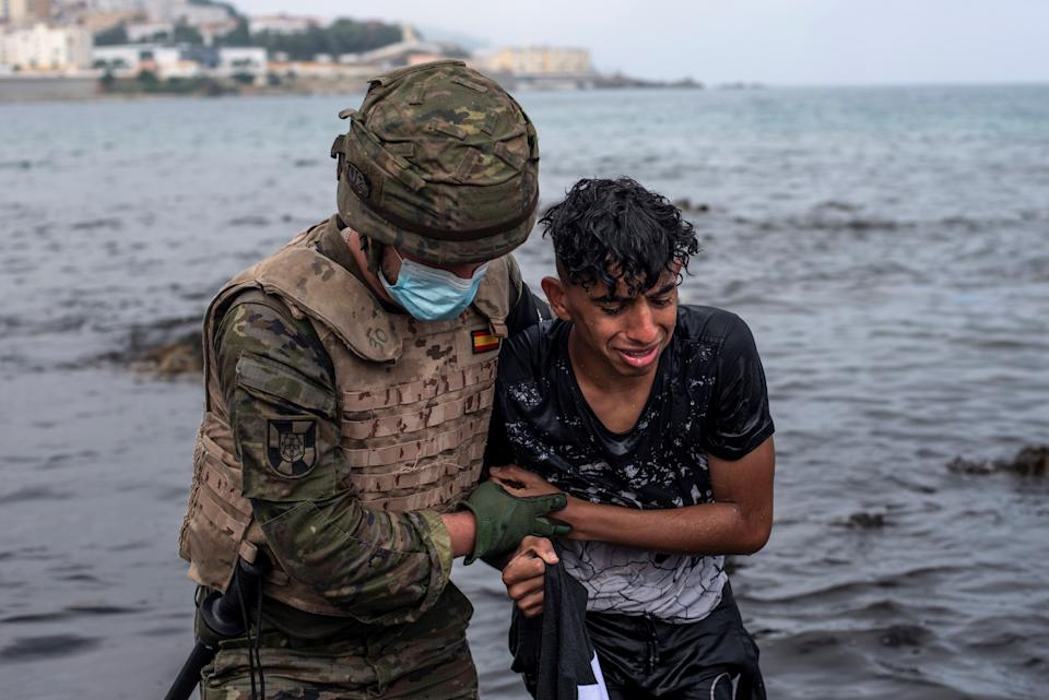 A Spanish soldier helps a migrant at his arrival at El Tarajal beach, in Ceuta, Spain. Source: EPA