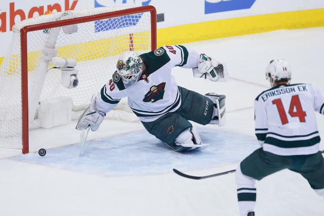 Minnesota Wild goaltender Devan Dubnyk (40) scrambles for a puck that bounced off his leg during the first period in Game 5 of the team's NHL hockey first-round playoff series against the Winnipeg Jets in Winnipeg, Manitoba, Friday, April 20, 2018. (John Woods/The Canadian Press via AP)