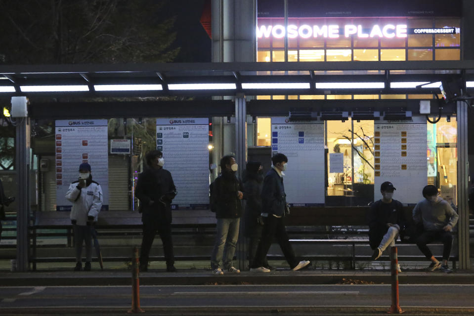 People wearing face masks to help protect against the spread of the coronavirus wait for buses at a bus station in Goyang, South Korea, Sunday, Nov. 22, 2020. South Korea says it will impose stricter social distancing rules in the greater Seoul area to fight a coronavirus resurgence, as the country registered more than 300 new cases for the fifth straight day. (AP Photo/Ahn Young-joon)