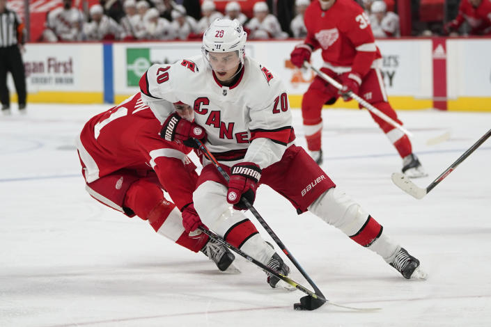 Carolina Hurricanes right wing Sebastian Aho (20) protects the puck from Detroit Red Wings center Dylan Larkin (71) in the second period of an NHL hockey game Sunday, March 14, 2021, in Detroit. (AP Photo/Paul Sancya)