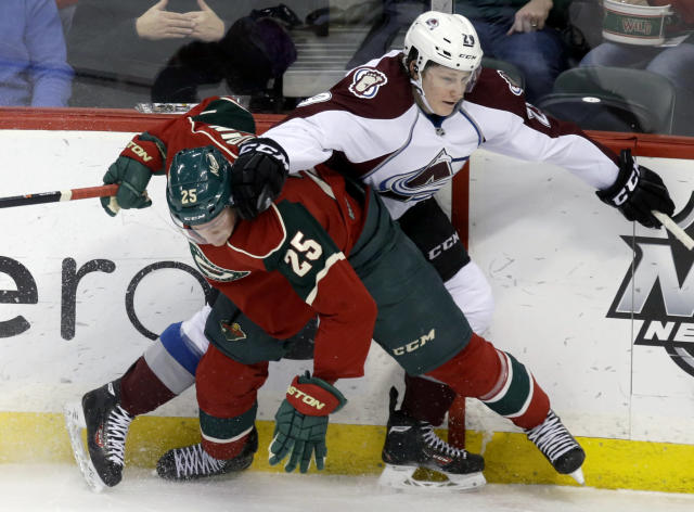 Colorado Avalanche's Nathan MacKinnon, right, and Minnesota Wild's Jonas Brodin, of Sweden, gets tangled up along the boards in the first period of an NHL hockey game, Saturday, Jan. 11, 2014, in St. Paul, Minn. (AP Photo/Jim Mone)