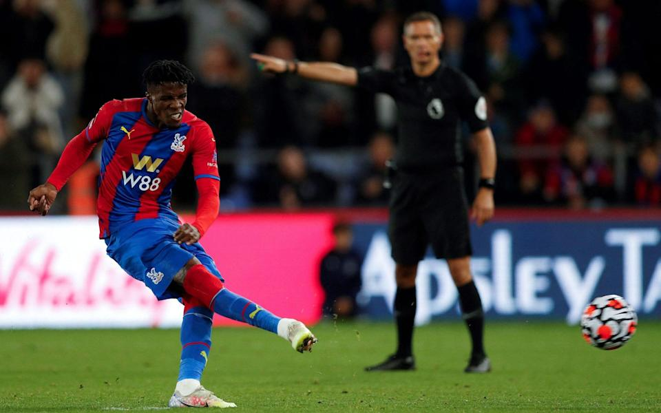 Crystal Palace's Ivorian striker Wilfried Zaha scores the opening goal from the penalty spot during the English Premier League football match between Crystal Palace and Brighton - ADRIAN DENNIS/AFP via Getty Images