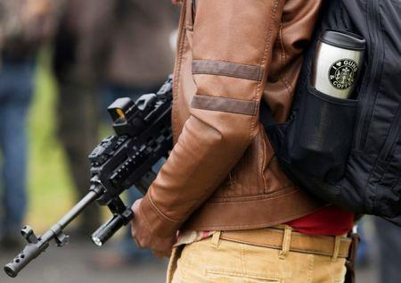 Williams holds a firearm as he attends a rally against Initiative 594 at the state capitol in Olympia, Washington
