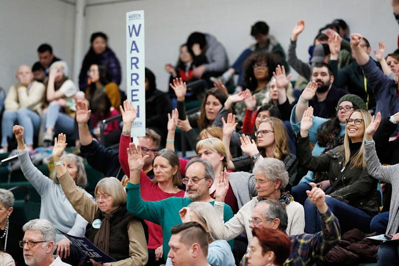 Supporters for Sen. Elizabeth Warren raise their hands to be counted at a caucus site during the Iowa Democratic caucus at Hoover High School, in Des Moines, Iowa, on Monday.   Charlie Neibergall/AP/Shutterstock