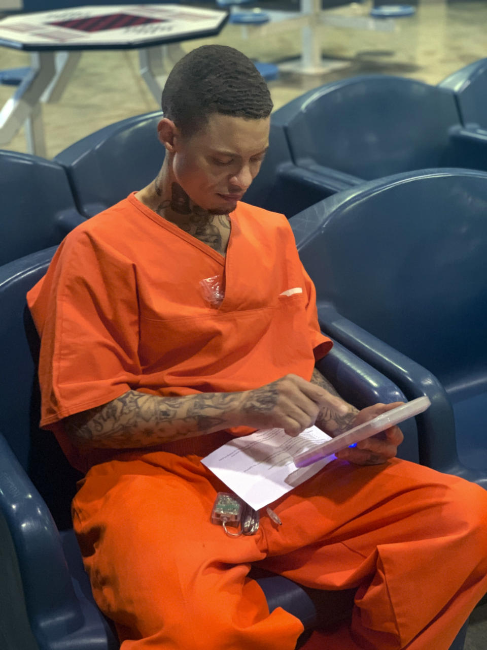 In a photo provided by the North Fork Correctional Center in Sayre, Okla., on Tuesday, June 9, 2021, inmate Byron Robinson works on a new Securus tablet, which are being provided for free to Oklahoma inmates as part of a new program by the Department of Corrections. Robinson, who has been incarcerated since 2005, the same year YouTube was founded, said it was the first time he'd ever held a computer tablet. The devices will include free content like access to a law library, along with some podcasts, books and educational materials. (Lance West/Oklahoma Department of Corrections via AP)